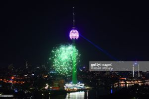 Fireworks explode around the lit-up Lotus Tower in Colombo on September 16, 2019. - Sri Lanka on September 16 opened a Chinese-backed massive partially built tower plagued by corruption allegations, one of the white elephants started during the former strongman president's regime.