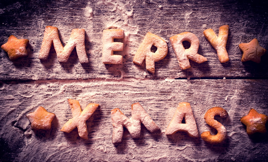 Merry Xmas text with cookies in the wooden background from above