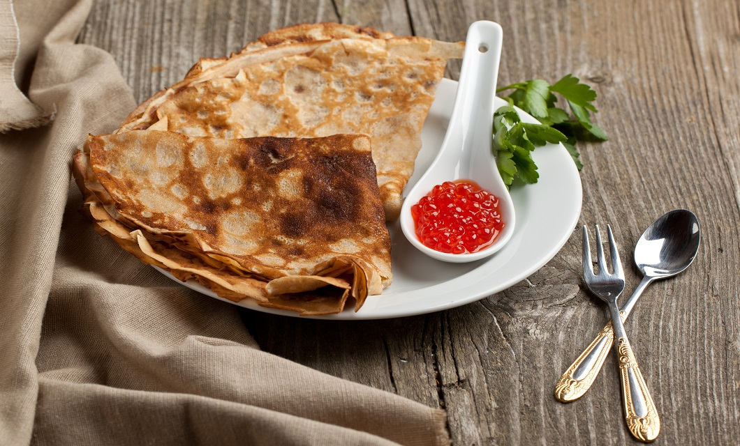 Plate of pancakes with red caviar and twig of parsley served with tableware on old wooden table