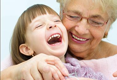 Isoäiti opettaa virkkaamista nauravalle pikkutytölle