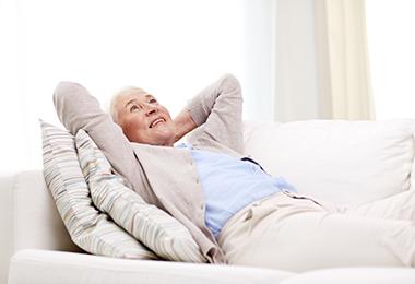 Vanhempi nainen ottaa rennosti kotisohvalla