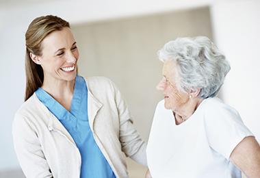Hoitotyöntekijä ja iäkäs nainen hymyilevät toisilleen yhdessä kulkiessaan