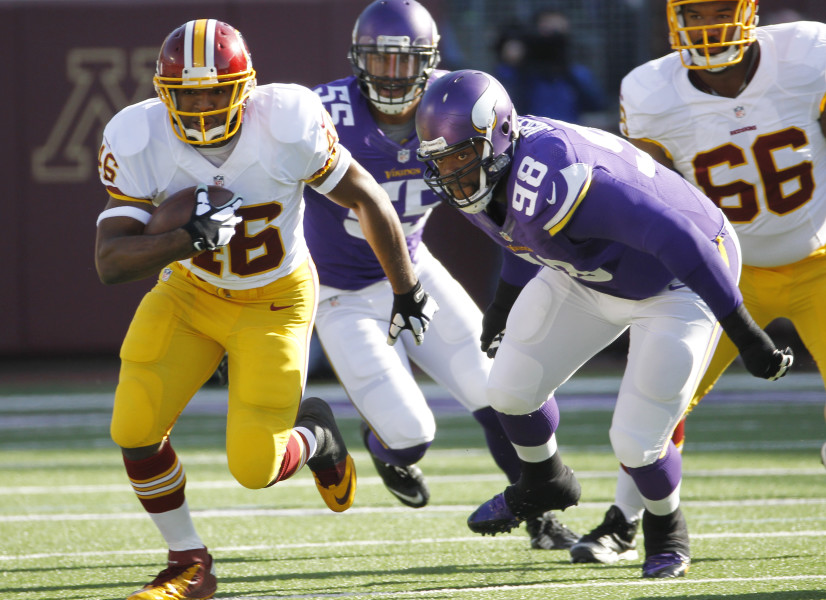 Washington Redskins running back Alfred Morris, left, runs from Minnesota Vikings defensive tackle Linval Joseph (98) during the first half of an NFL football game, Sunday, Nov. 2, 2014, in Minneapolis. (AP Photo/Ann Heisenfelt)