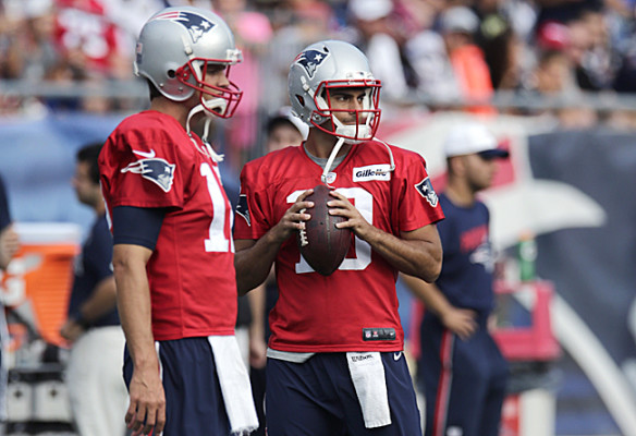 New England Patriots quarterback Jimmy Garoppolo, right, clutches the football as he stands with Tom Brady at an NFL football training camp, Wednesday, Aug. 5, 2015, in Foxborough, Mass. (AP Photo/Charles Krupa)