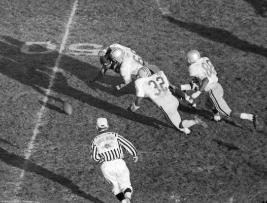 Halfback O.J. Simpson, almost hidden by Ohio State's middle guard Jim Stillwagon (68), fumbles as he's hit during Rose Bowl game in Pasadena, California on Jan. 1, 1969. Ohio State recovered and went on to score a field goal that put the Buckeyes in the lead. Other Ohio State players are linebacker John Tatum (32) and end Dave Whitfield. (AP Photo)