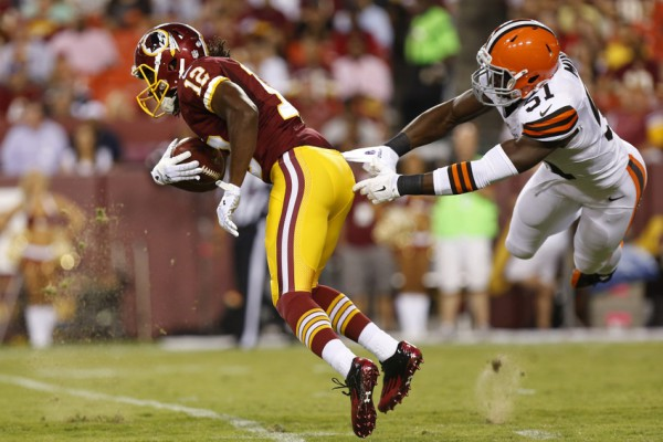 Aug 18, 2014; Landover, MD, USA; Washington Redskins wide receiver Andre Roberts (12) returns a punt past Cleveland Browns linebacker Barkevious Mingo (51) in the first quarter at FedEx Field. Mandatory Credit: Geoff Burke-USA TODAY Sports