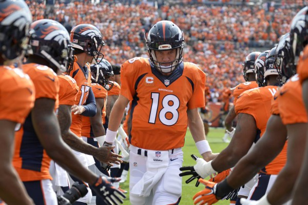Sep 13, 2015; Denver, CO, USA; Denver Broncos quarterback Peyton Manning (18) high fives teammates prior to their game against the Baltimore Ravens at Sports Authority Field at Mile High. Mandatory Credit: Ron Chenoy-USA TODAY Sports ORG XMIT: USATSI-224472 ORIG FILE ID:  20150913_ads_ac4_073.JPG