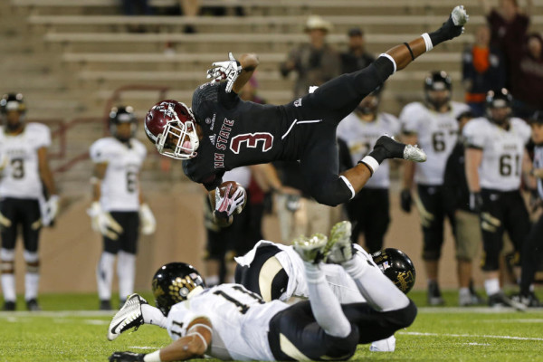 New Mexico State running back Larry Rose III (3) goes airborne after being tripped by Idaho cornerback Kendrick Trotter and safety Russell Siavii (11) during the second half of an NCAA college football game in Las Cruces, N.M., Saturday, Oct. 31, 2015. New Mexico State won 55-48. (AP Photo/Andres Leighton)