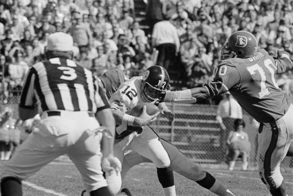 27 Sep 1970, Denver, Colorado, USA --- Denver Bronco tackle (#70) Paul Smith begins his tackle on Pittsburgh quarterback (#12) Terry Bradshaw eye level. Smith dropped the Steelers Bradshaw for a 12-yard 1st quarter loss. Denver won, 16-13. --- Image by © Bettmann/CORBIS