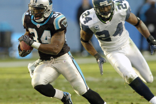 Carolina Panthers' DeAngelo Williams (34) runs past Seattle Seahawks' Deon Grant (24) for a touchdown in the fourth quarter of the Panthers' 13-10 win in an NFL football game in Charlotte, N.C., Sunday, Dec. 16, 2007. (AP Photo/Mike McCarn)
