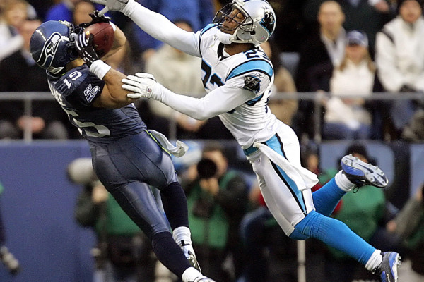 ** FILE ** Seattle Seahawks' Seneca Wallace, left, makes an over-the-shoulder reception as Carolina Panthers' Ken Lucas defends in the NFC championship football game in this Jan. 22, 2006 file photo in Seattle. The catch came during the first game of Wallace's career in which he played wide receiver, but five months later, Wallace is looking for more action as he sits as back-up quarterback and waits for the Seahawks to sign a veteran backup passer to free Wallace to play receiver. (AP Photo/Elaine Thompson, File)