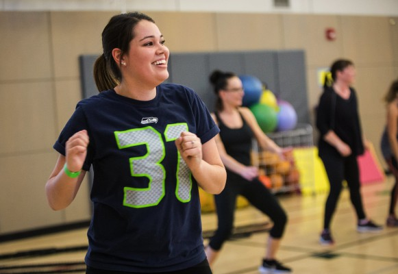 "Ellie Boswell, wearing a Kam Chancellor Seahawks shirt, smiles as she does warmup exercises in line with other ladies during a Form by Force Women's Boot Camp at the Gymnasium at Les Gove Park in Auburn on Wednesday, March 30, 2016. The Seahawks safety hosts the workouts, along with Kevin Allen, his personal trainer and co-owner of Form by Force. ""Special guests,"" like teammate Richard Sherman, sometimes make appearances."