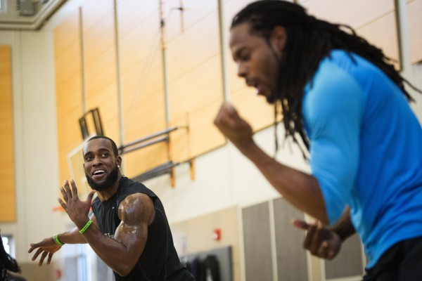 "Seahawks strong safety Kam Chancellor looks over at teammate, cornerback Richard Sherman, who dropped in as a special guest, during a Form by Force Women's Boot Camp at the Gymnasium at Les Gove Park in Auburn on Wednesday, March 30, 2016. The Seahawks safety hosts the workouts, along with Kevin Allen, his personal trainer and co-owner of Form by Force. ""Special guests,"" like teammate Richard Sherman, sometimes make appearances."