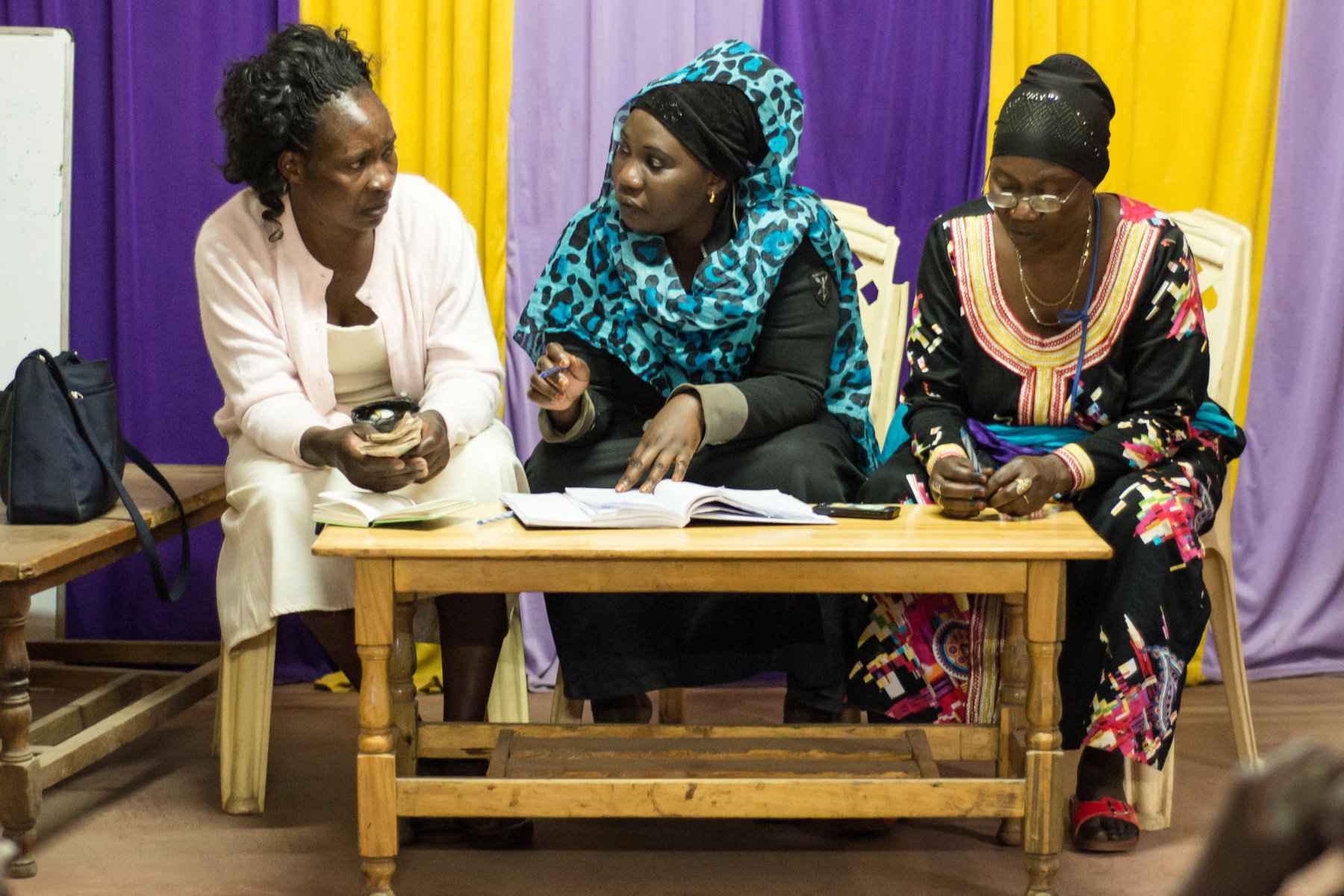 Officials of Maji Mazuri savings group – the treasurer, secetary and chairperson - discuss during their group meeting