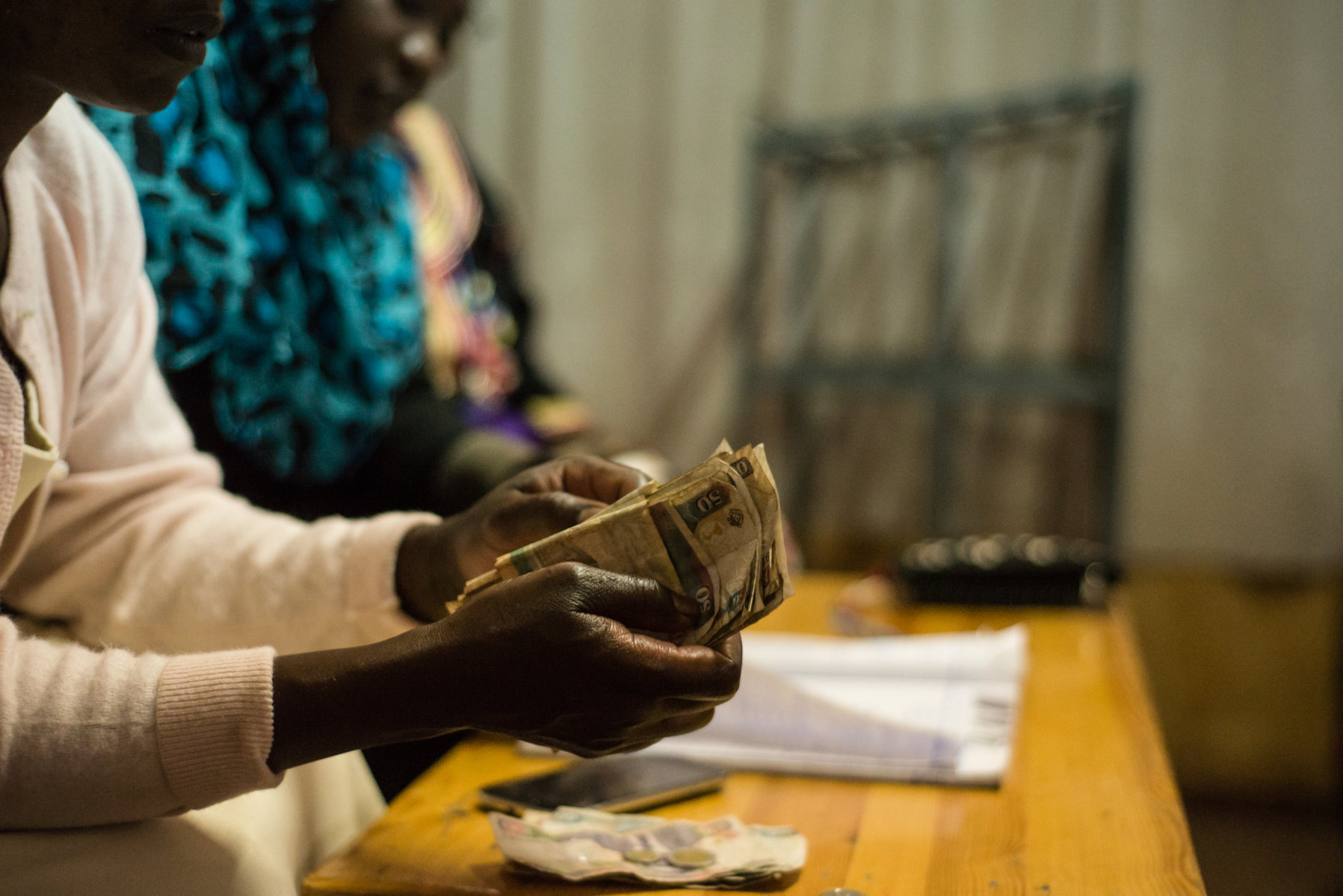 Treasurer of Maji Mazuri savings groups counts money during the meeting