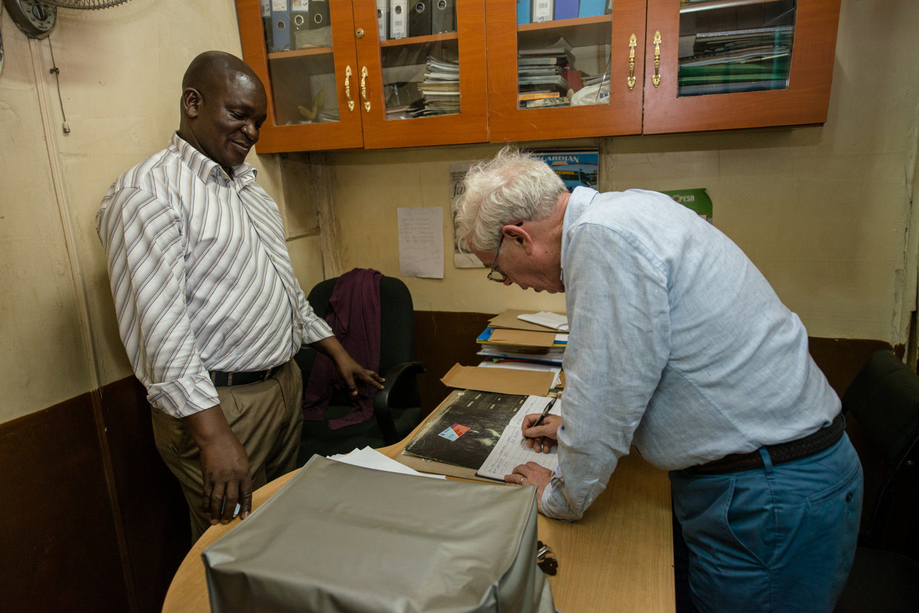 John Kay signs the visitors book at Haki Group offices as the Chief Executive Officer, Charles Ogutu looks on.