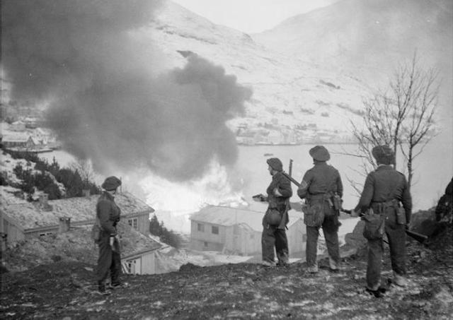 Foto: Britiske soldater ser et tysk ammunisjonslager i brann under Måløyraidet. Foto: Malindine, E G/Imperial War Museums. Offentlig eiendom.