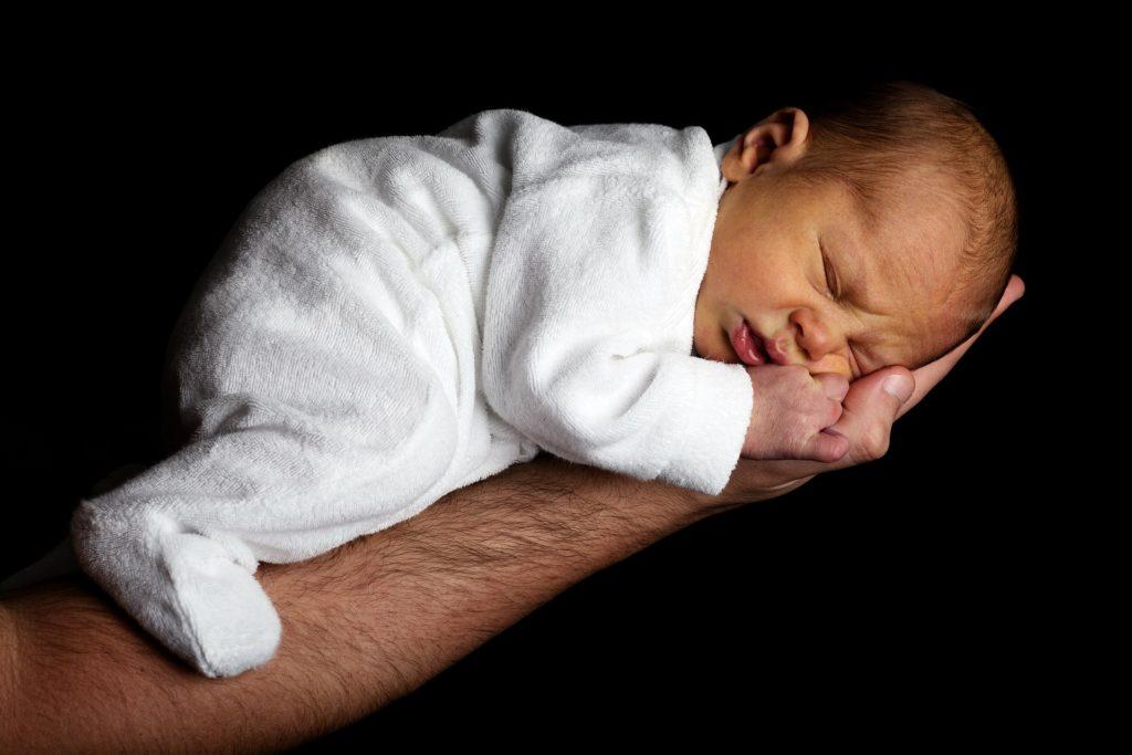 Spedbarn som sover på arm.