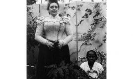 Portret van mevrouw Ponse met een bediende voor een kamerscherm in de tuin, omstreeks 1900.