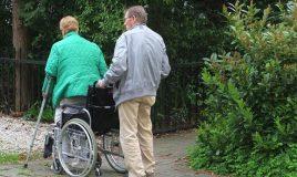 mantelzorg man helpt vrouw in rolstoel