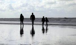 familie wandelt op strand