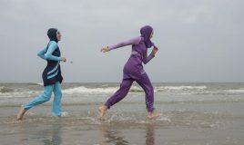 vrouwen in boerkini lopen de zee in