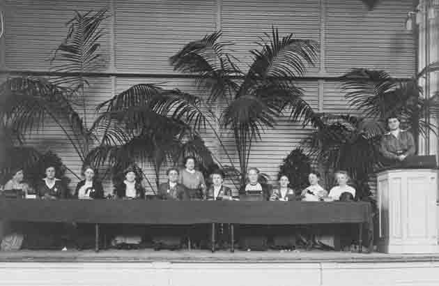 congreszaal met 12 deelneemster op het podium van het international congress of women 1915