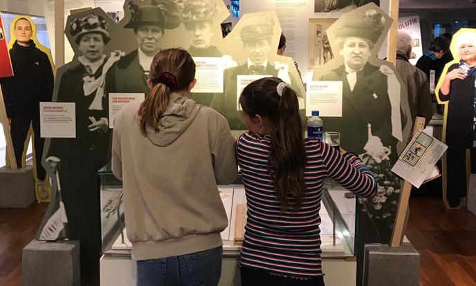 twee jonge meiden bekijken een vitrine op tentoonstelling de straat op van atria en oba