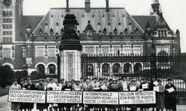 groep vrouwen voor het vredespaleis in Den Haag met borden met tekst: '100.000 handteekening 20 organisaties met ca 135.000 leden'; 'opdracht der volken aan regeeringen der heele wereld'; 'Internationale Vrouwenbond voor Vrede en Vrijheid'; 'wij zijn besloten een eind te maken aan de oorlog!'.