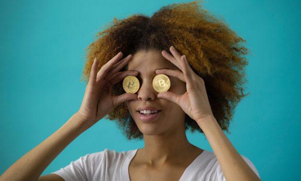 zwarte vrouw die 2 munten voor haar ogen houdt