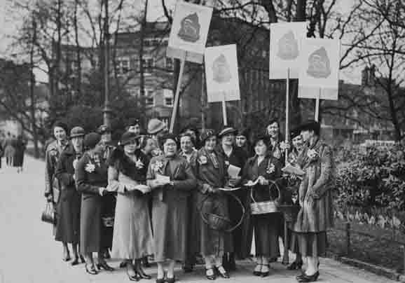 Vrouwen met protestborden met tekst 'Propaganda week van het comité ter bevordering van de waardering van vrouwenarbeid in het gezin en maatschappij 28 maart - 4 april'
