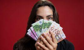 vrouw die haar gezicht bedekt met geld