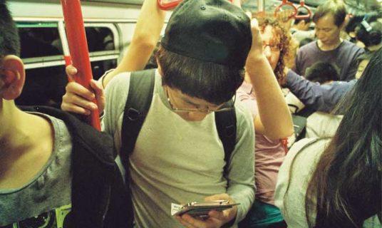 jongen in metro checkt actueel nieuws op mobieltje