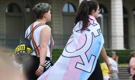 jonge-mensen-op-straat-met-vlag-met-man-vrouw-symbool
