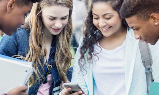 4 jongeren kijken op een telefoon