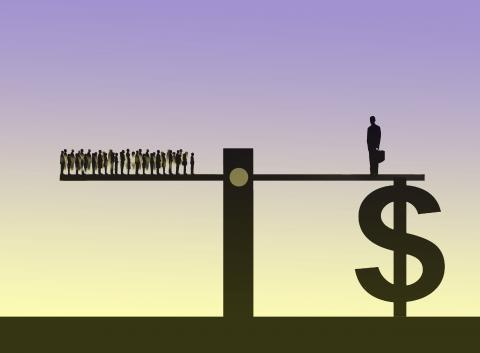 large group of people standing on a see saw with a businessman supported by a large dollar standing on the other showing a disproportionate distribution of wealth and resource.