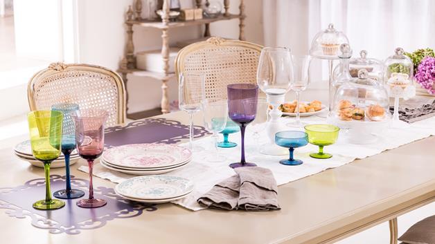 A tavola con colore e stile: bicchieri colorati si mischiano ad una mise en place classica, fatta di piatti finemente decorati da disegni classici.