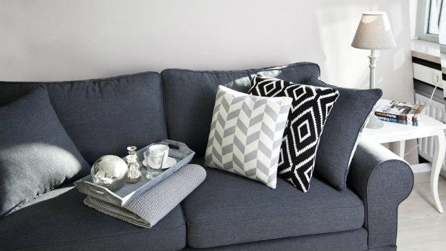 soggiorno grigio divano cuscini vassoio plaid