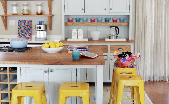 Białe meble kuchenne i żółte taborety