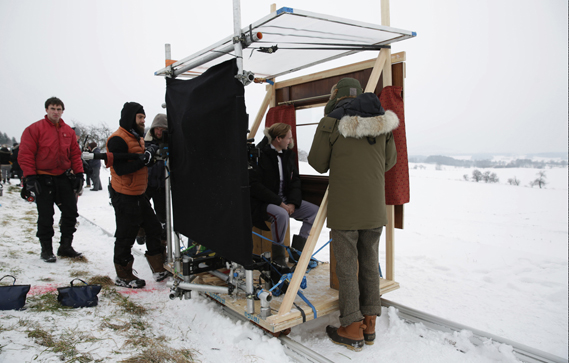 Anderson directs Ralph Fiennes looking through the window of a 'train', actually a window frame mounted on a plywood platform attached to a dolly on rails. Photo: Martin Scali