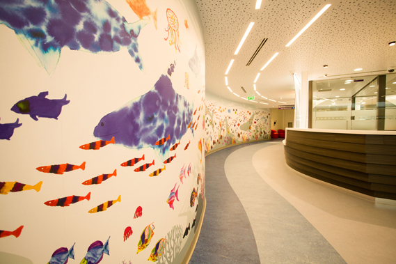 Seascape mural (and boat reception desk) in the main entrance to Great Ormond Street Hospital, London. Children at the hospital designed the fish during a workshop with artist Isobel Manning; each was then scanned and arranged into a 20-metre display by studio Sable & Hawkes. Photo by Ash Knoteck