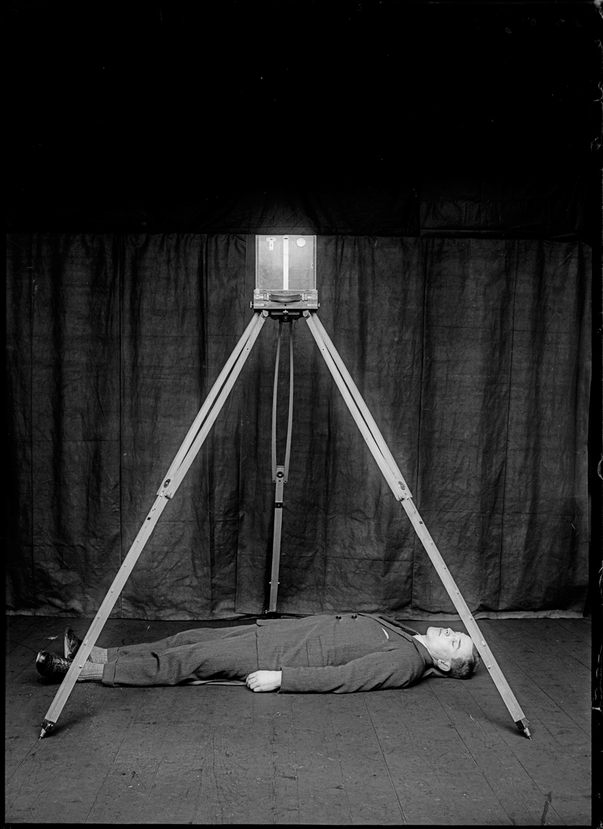 Rodolphe A Reiss, Demonstration of the Bertillon metric photography system, 1925. © RA Reiss, courtesy of Collection of the Institut de Police Scientifique et de Criminologie de l'Université de Lausanne. In addition to the two-metre high tripod, Bertillon's system of 'metric photography' used 'perspectometric' grids which enabled investigators to calculate the dimensions of a particular space and the various objects within it