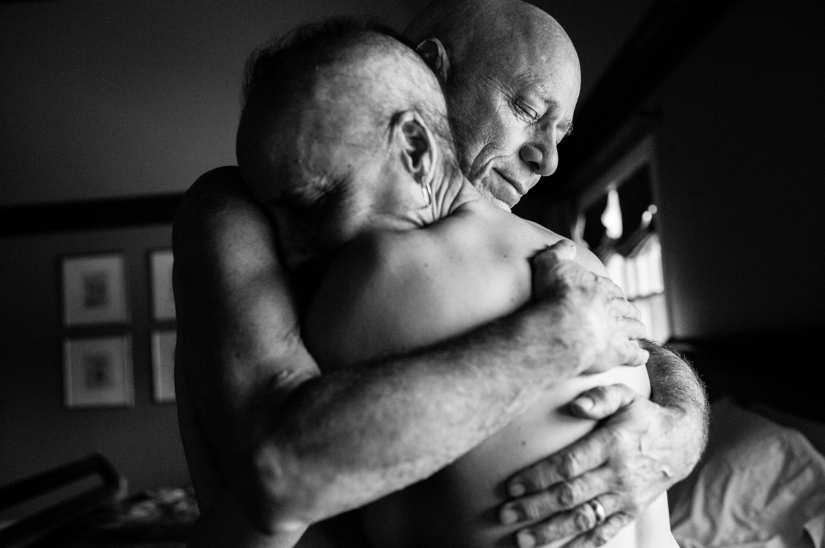 A Life in Death, Nancy Borowick, USA, 2015. Borowick photographs her own parents who were in parallel treatment for stage-four cancer, side by side. MArried for thirty years, Howie and Laurel Borowick embrace in the bedroom of their home.  Chappaqua, New York. March 2013.