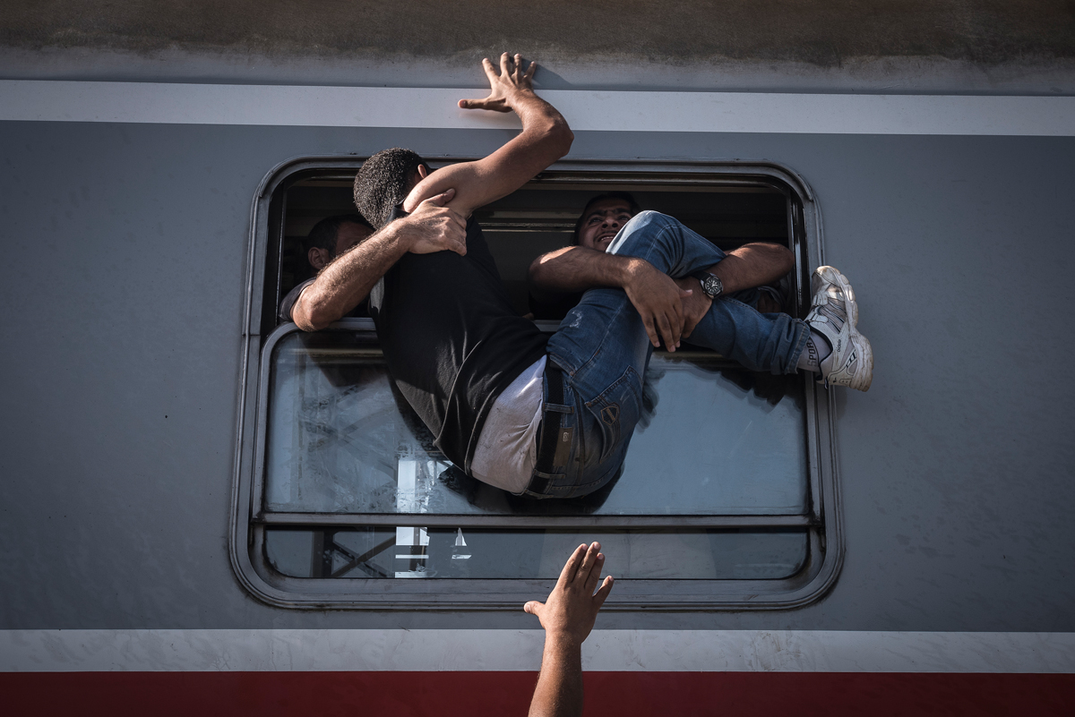 The New York Times, Sergey Ponomarev, Russia, 2015. Migrants struggle to climb onto a train headed to Zagreb, the Croatian capital.
