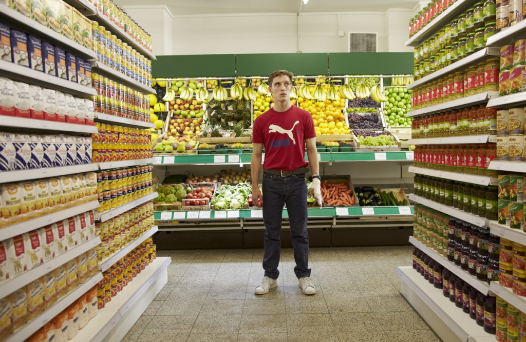 "Szene 1.24 Bonn-Supermarkt / Gang. Martin (Jonas Nay) entdeckt den ""goldenen Westen"". Tischbier kommt um die Ecke..."