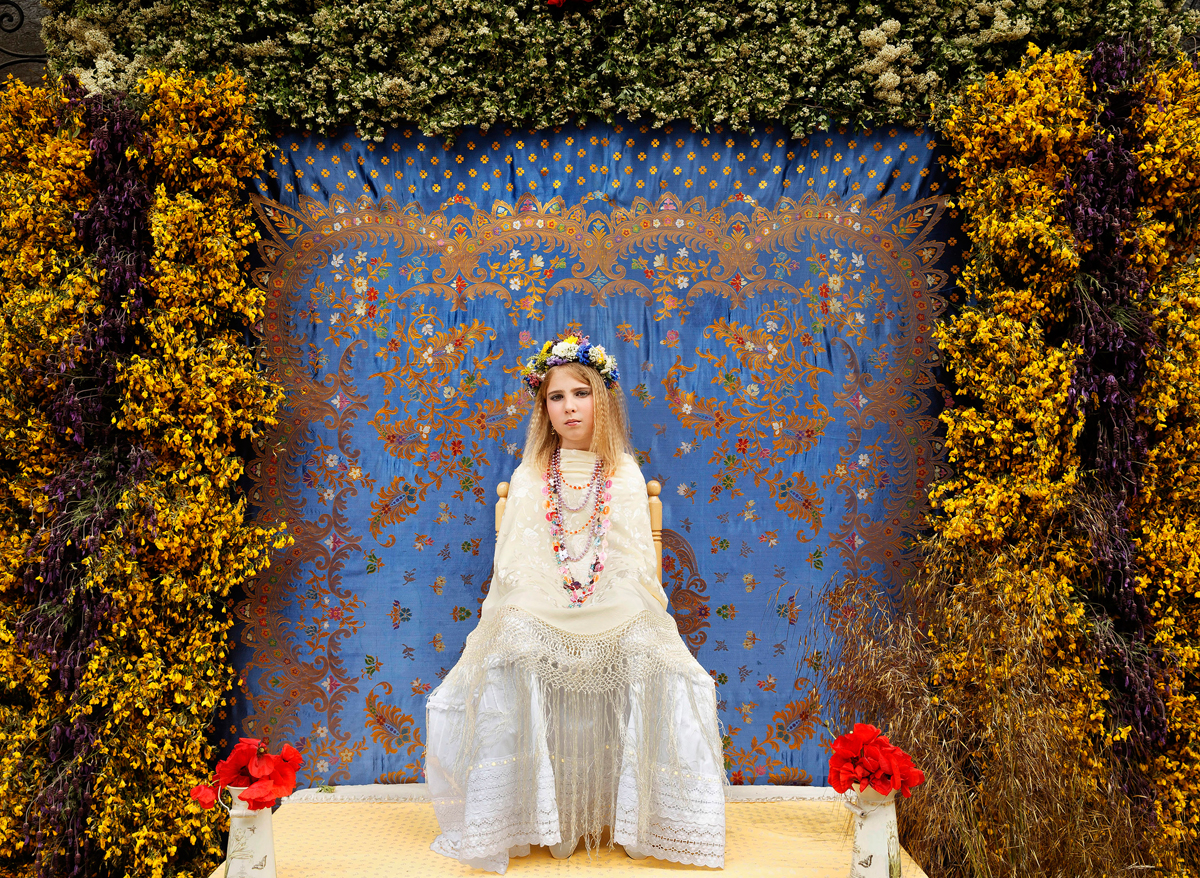 A 'Maya' girl sits in an altar during the traditional celebration of 'Las Mayas' on the streets of the small village of Colmenar Viejo, near Madrid, Spain on Saturday, May 2, 2015. The festivity of 'Las Mayas' comes from pagan rites and dates from at least the medieval age, appearing in ancient documents. It takes place every year in the beginning of May and celebrates the arrival of the spring. A girl between 7 and 11years is chosen as 'Maya' and should sit still, serious, and quiet for a couple of hours in an altar on the street decorated with flowers and plants, afterwards they walk to the church with their family where they attend a ceremony. Not more than four, or five girls are chosen as a Maya each year.