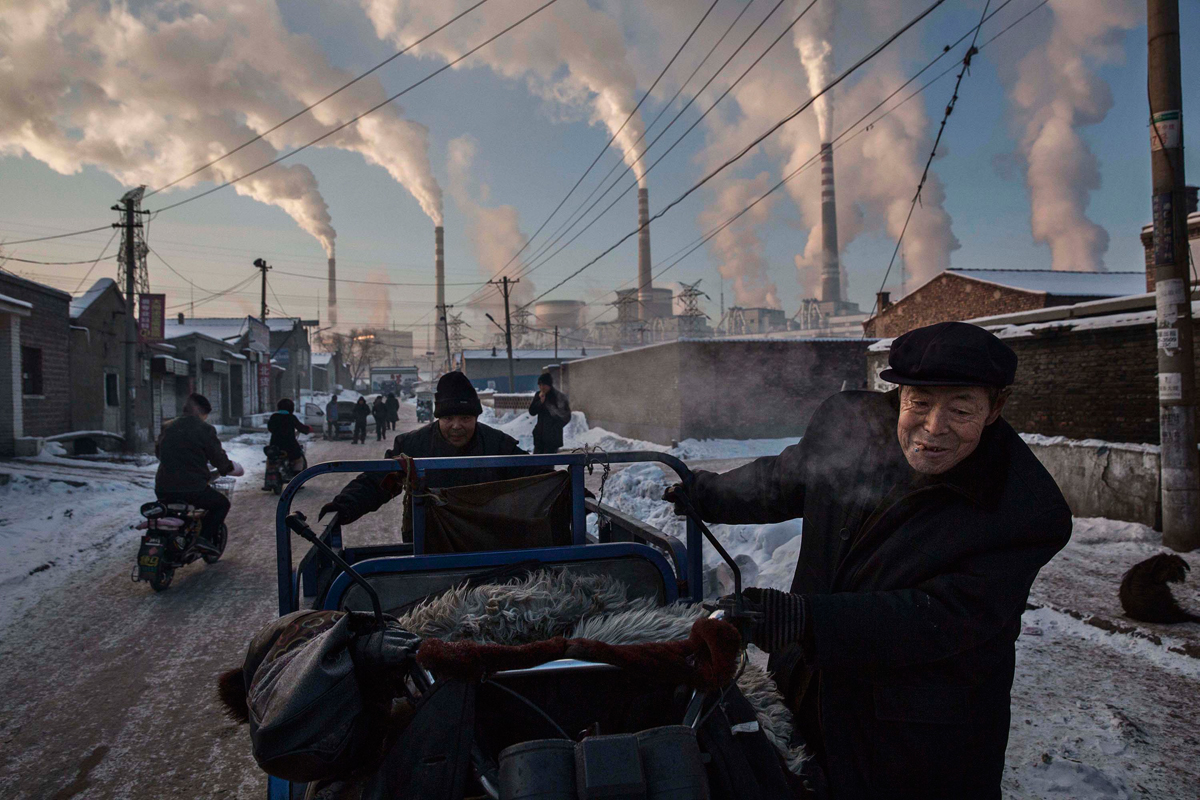 China's Coal Addiction, Kevin Frayer, Canada, 2015, Getty Images. Chinese men pull a tricycle in a neighborhood next to a coal-fired power plant in Shanxi, China, on 26 November 2015. A history of heavy dependence on burning coal for energy has made China the source of nearly a third of the world's total carbon dioxide (CO2) emissions, the toxic pollutants widely cited by scientists and environmentalists as the primary cause of global warming.