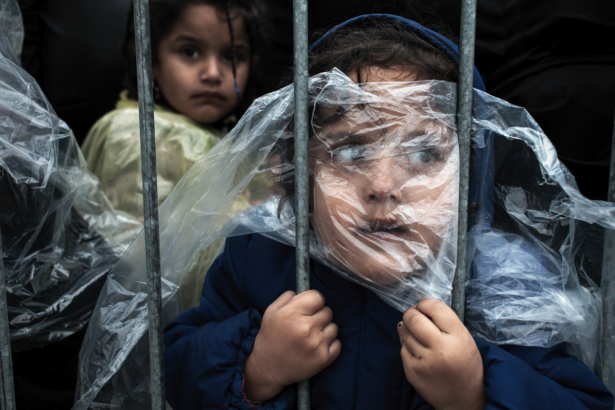 Waiting to Register, Matic Zorman, Slovenia, 2015. A child is covered with a raincoat while she waits in line to register at a refugee camp in Preševo, Serbia, 07 October 2015.