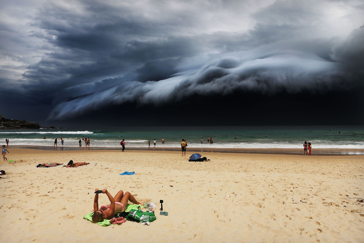 "Storm Front on Bondi Beach, Rohan Kelly, Australia, 2015, Daily Telegraph. Sunbather oblivious to the ominous shelf cloud approaching - on Bondi beach. A massive ""cloud tsunami"" looms over Sydney in a spectacular weather event seen only a few times a year."