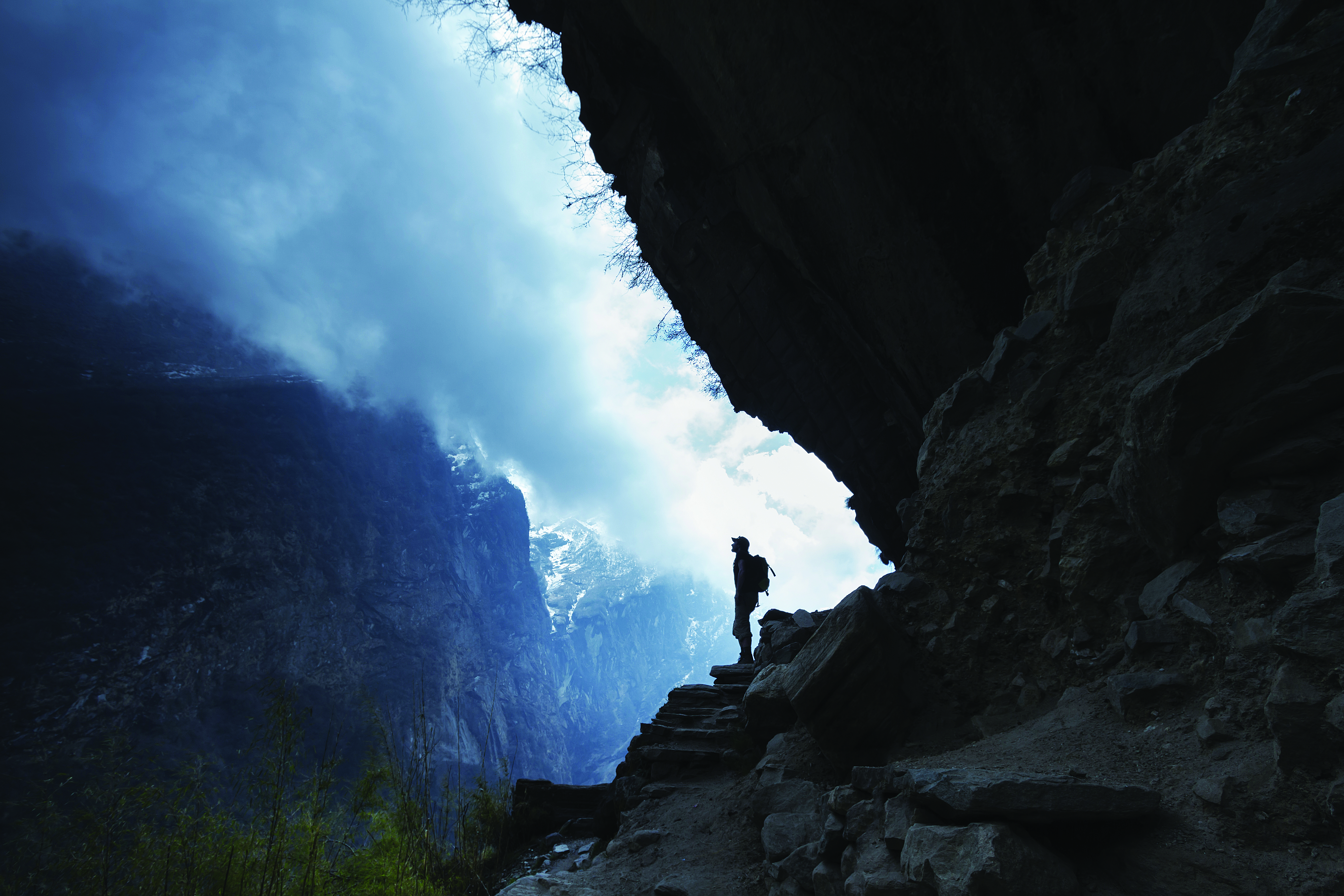 Trekker watching storm clouds move into a valley (Picturegarden/Getty Images)